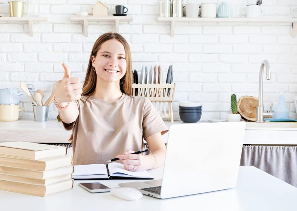 Young smiling student girl showing thumb up studying online, e-learning