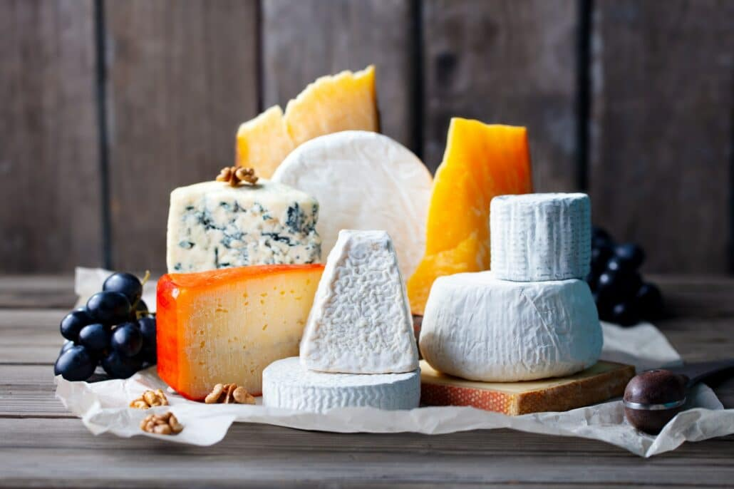 Cheese assortment: blue cheese, hard cheese, soft cheese on a parchment paper. Wooden background.
